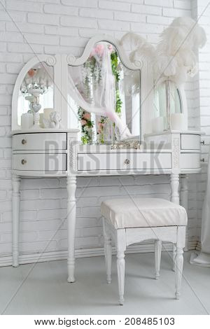 White Boudoir Table With Mirror, Casket, Candles And Feathers On It Near Brick Wall In White Room, F
