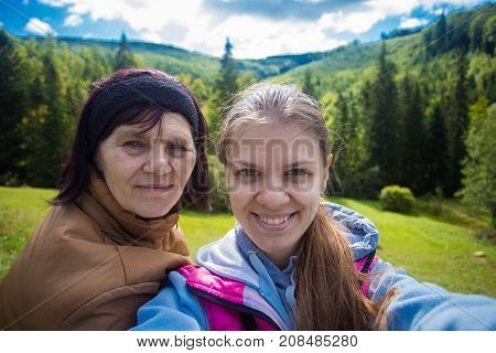 Mom and adult daughter sitting on the top of mountains and taking selfie. Happy senior women and daughter taking selfie together. Holiday daughter with mother