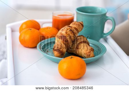 Classic food for healthy breakfast. Plate of fresh croissants, tangerines, a glass of freesia, a mug of coffee on a rustic wooden table.