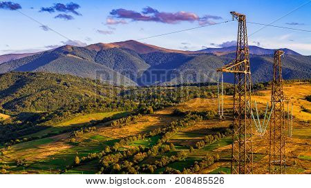 High voltage lines and and power pylons against the background of a beautiful autumn landscape in the Carpathian Mountains.