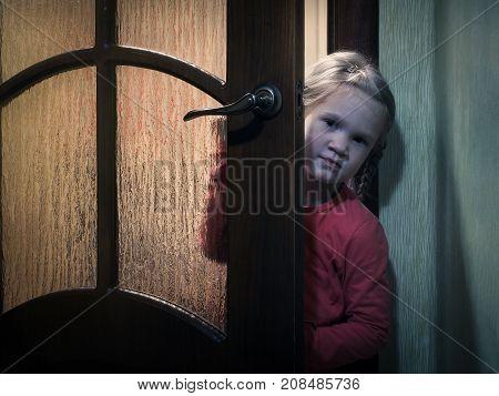 A child Peeps standing behind a door in a dark room