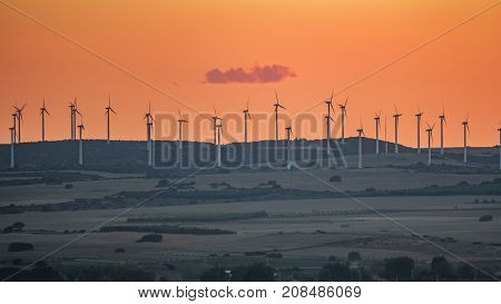 Orange sunset over windmill array over hill