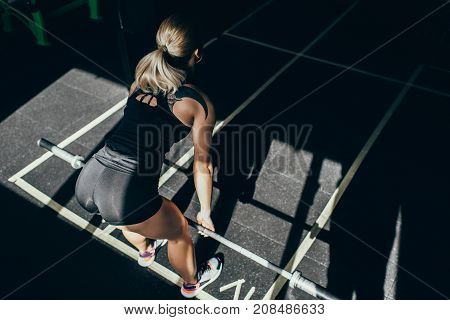 Sportswoman Lifting Barbell In Gym
