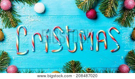 Image of Christmas table with spruce branches and colorful balls , congratulations from caramel canes, empty space for text