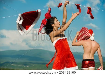Couple in love of man and girl hanging clothes for drying. New year guy with muscular body on blue sky. Christmas man and woman family. Laundry and dry cleaning. Xmas red costume on rope with pin.