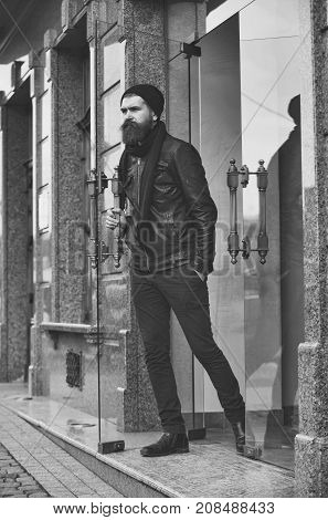 bearded man long beard brutal caucasian hipster with moustache on serious face in black leather jacket hat pants exit out of glass door unshaven guy with stylish hair outdoor