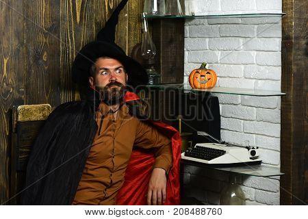Halloween Wizard Sitting At Pumpkin, Typewriter, Books On Shelves