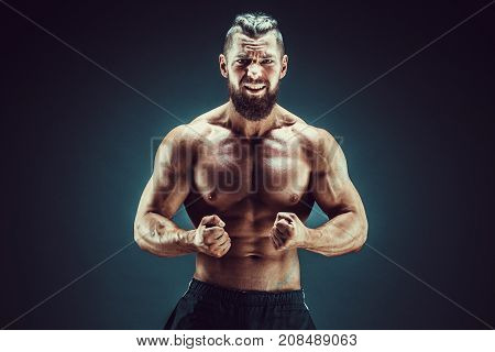 Very brawny guy bodybuilder posing, roar. Beautiful sporty guy male power. Fitness muscled man in studio. Dark background.