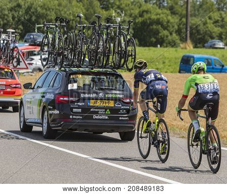 Mailleroncourt-Saint-Pancras France - July 5 2017: Rear image of two cyclistsriding behind a technical car on a road to La Planche des Belle Filles during the stage 5 of Tour de France 2017