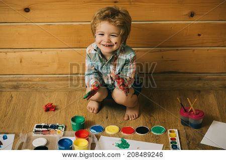 Boy painter painting on wooden floor. Child happy smiling colored hands gouache paints and drawings. Arts and crafts. Imagination creativity and freedom concept. Kid learning and playing.