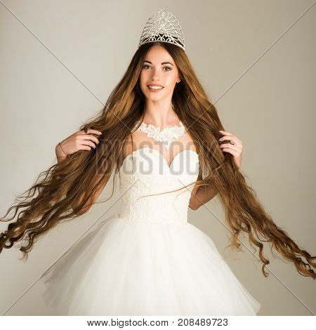 Beauty salon and wedding fashion. Girl has fashionable makeup and healthy hair on grey background. Haircare and prom queen. Hairdresser and cosmetics. Woman with long hair white dress and crown.