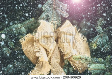 New year or christmas bow decoration of sackcloth with golden thread on natural green fir tree background in snow snowflakes