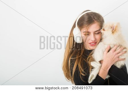 Xmas party and vacation. Girl with happy face in gloves and ears. Dog in hand of woman on white background. Woman with small dog of Pomeranian Spitz. New year of dog and winter holiday celebration.