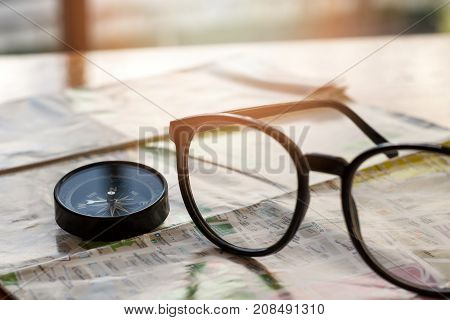 Compass and eye glasses on map travel concept