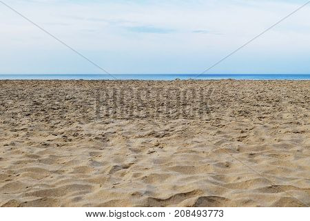 Tattered sandy beach on the Arabian Sea with a thin strip of sea