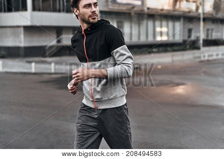 Chasing empty streets. Handsome young man in sport clothing looking away while running outdoors