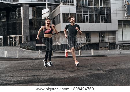 Side by side through the city. Full length of young couple in sport clothing running through the city street together