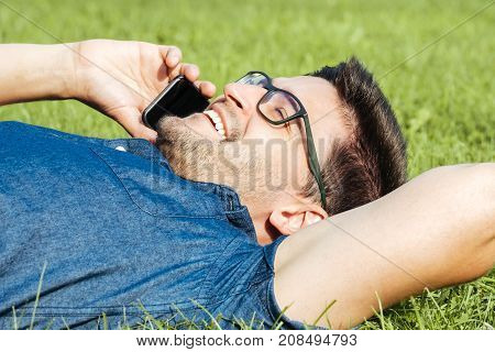 Young Man Using Mobile Phone While Lying On Grass