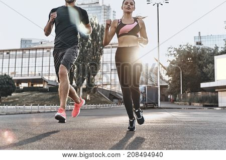 Enjoying good run. Young couple in sport clothing running through the city street together