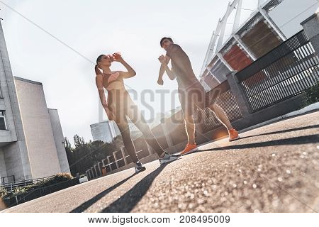 Taking a timeout. Full length of young couple in sport clothing having a pause to drink water while exercising outdoors
