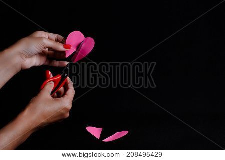 The picture is made on a dark background. The woman cuts the paper heart.