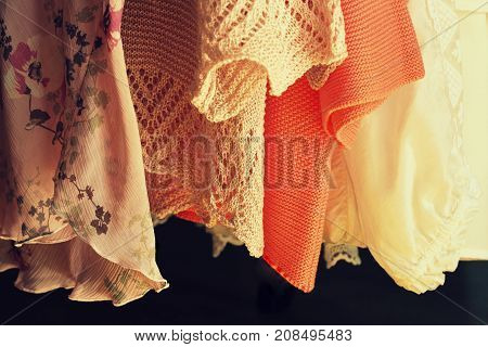 Women clothes hanging on racks in a boutique store .