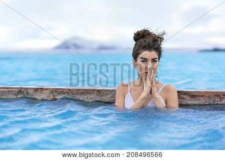 Charming girl in a white swimsuit relaxing in the geothermal pool on the background of snow mountains and cloudy sky outdoors in Iceland. She looks into the camera and holds her palms together.