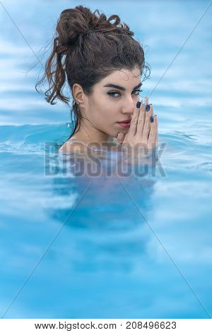 Tender girl in a white swimsuit relaxing in the geothermal pool outdoors in Iceland. She looks into the camera and holds her palms together in front of her face. Closeup. Vertical.