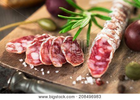 Sliced Salami and olives on rustic background