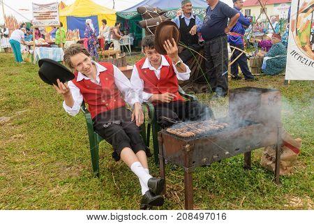 German Men Prepare Sausages And Welcome Visitors
