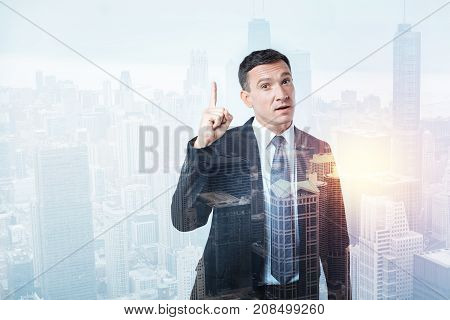 Unexpected decision. Clever attentive man in black suit looking concentrated while standing and pointing up to the sky