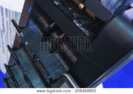 large device for recounting banknotes during cash withdrawals in a bank and a financial institution, the cashier's shop. Several trays for dispensing banknotes. Soft focus.