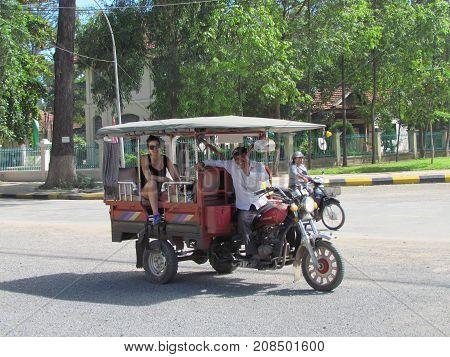Battambang, Cambodia, 29 September 2015:  Caucasian tourist woman and tuk tuk driver in a tuktuk car in the street