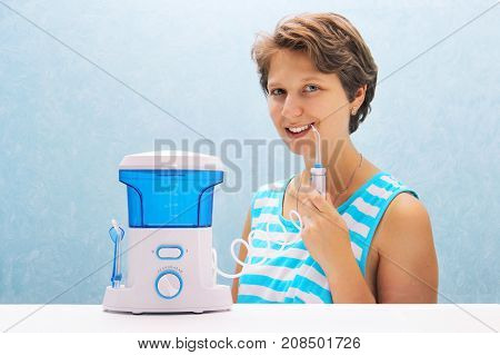 Beautiful Girl Flushes Her Teeth With An Oral Irrigator. The Woman Smiles And Holds The Irrigator Ha