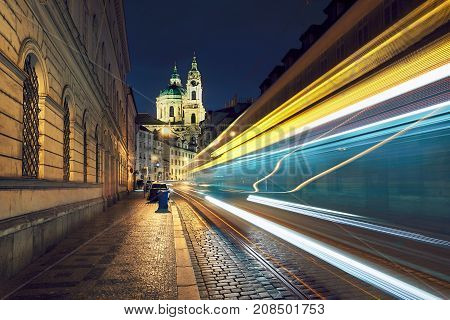 Night traffic on the ancient street near The Church of Saint Nicholas in Prague Czech Republic.