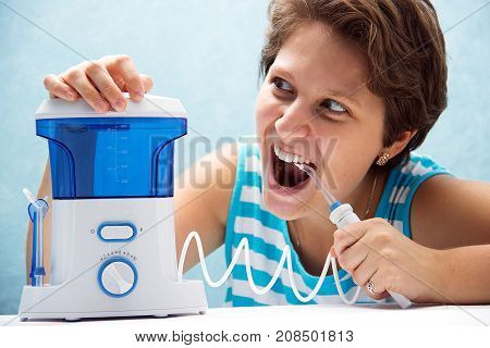 Beautiful And Crazy Girl Opened Her Mouth Wide And Brushed Her Teeth With An Irrigator With A Nozzle