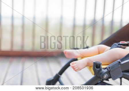Baby barefoot in stroller outdoors on wooden bridge in park