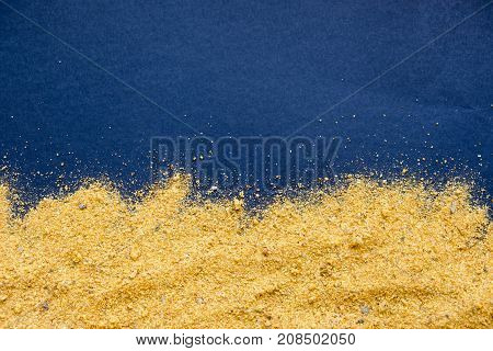 heap of curry powder on black slate background