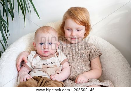 Boy with atopic dermatitis is sitting with his sister in a chair