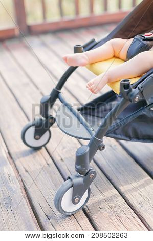Close-up of stroller with newborn baby sleeping outdoors on wooden pathway in park