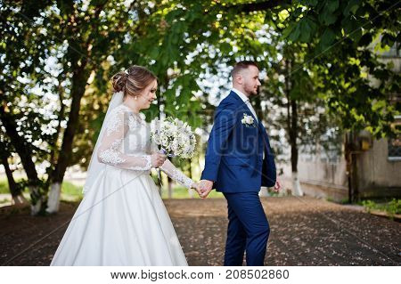 Lovely Newly Married Couple Walking In The Park On Their Wedding Day.