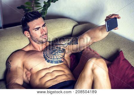 Handsome shirtless muscular bodybuilder man taking selfie with cell phone while laying on couch