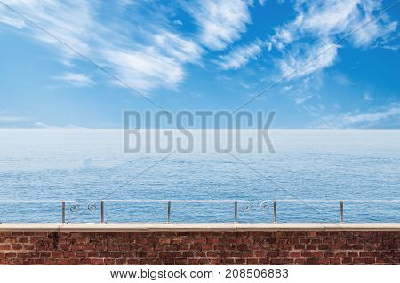 Calm sea and cloudy sky view with brick wall and railing in the foreground