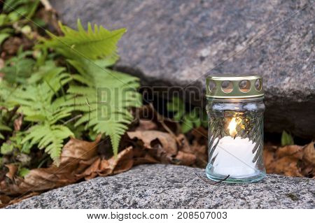 One votive candle standing on tombstone and burning. Stone grave green plants and old plant leaves seen in shallow background