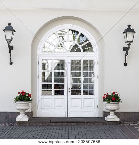 Elegant classic style glass paned front door with front lanterns and flower pots