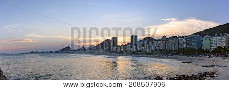 Panoramic photo of Leme and Copacabana beaches in Rio de Janeiro during sunset with its buildings but the mountains in the background