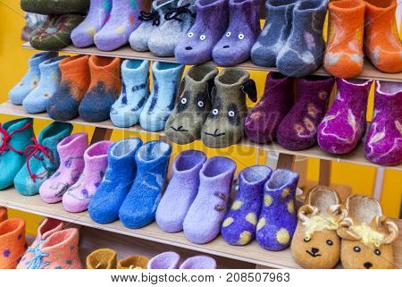 Colorful handmade children felt boots displayed in marketplace