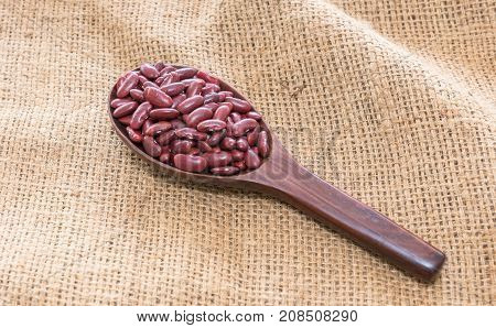 The background image of red beans in the wooden ladle on sackcloth .