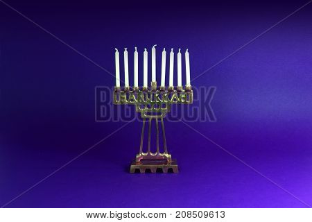 Brass Hanukkah menorah with white candles on a blue background