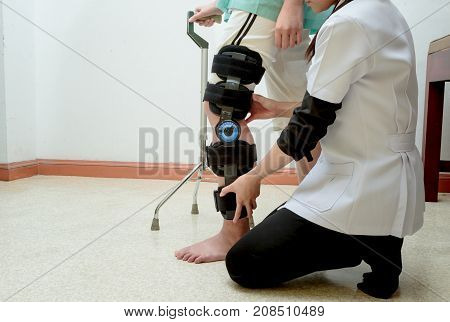 Physiotherapist assisting patient woman to walk using cane